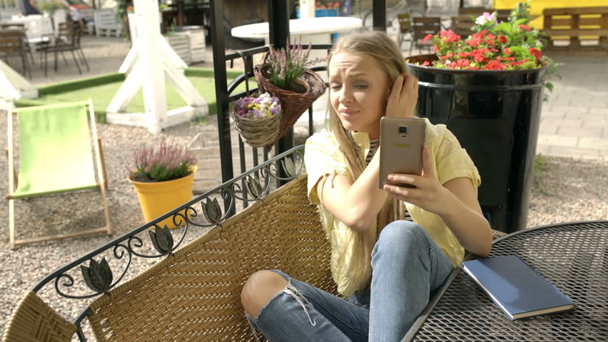 Pretty girl looks worried after having received bad news on smartphone