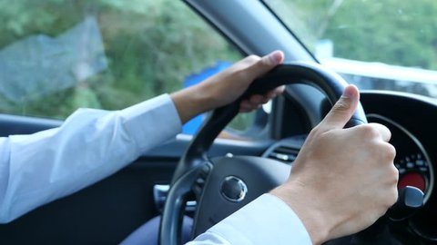 close-up of hands and steering wheel. A male businessman is driving a car . 4k, slow motion