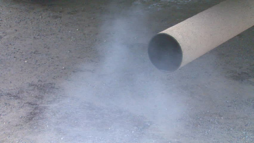 Exhaust emissions from a gasoline internal combustion engine spews from the truck's tailpipe.