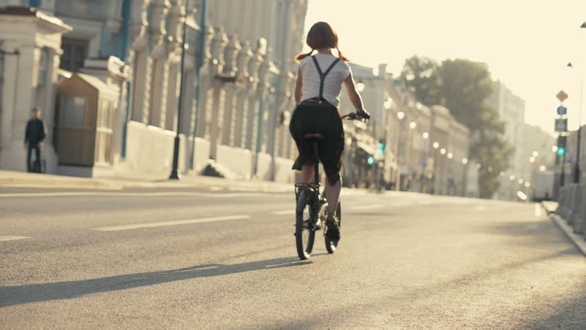 Ridding bicycle wheels close up. Yong Woman bicycle riding at city road on background traffic lights and houses. Woman bike city. Woman bike riding | Shutterstock HD Video #31256428