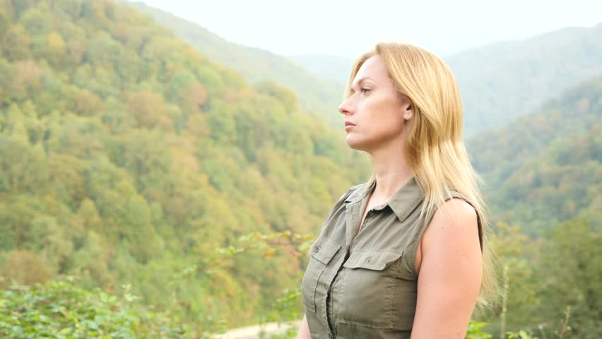 Close up portrait of beautiful young woman with blonde hair blowing in the wind looking at mountain. Slow Motion 4k   Shutterstock HD Video #31261852