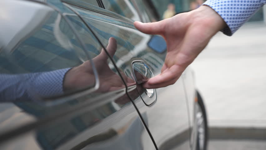 Hand of male businessman opens and holds the car door for the beautiful young woman. Man opening door of automobile for female passenger. Girl get into the auto. Close up Slow Motion