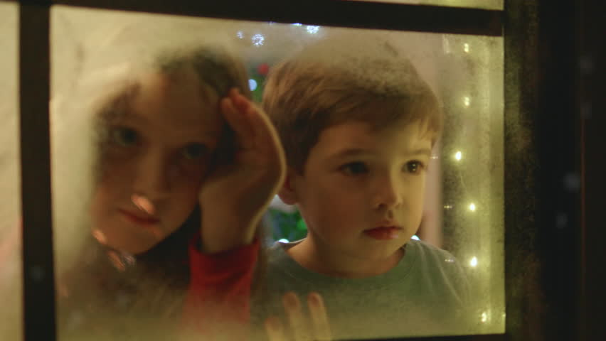 Adorable little boy and girl looking through the window and admiring first snow flakes and fireworks on Christmas evening.