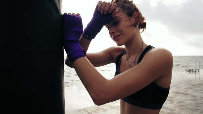 Closeup view of a young woman having a break after hard training by the boxing bag against the sun. Her hands are wrapped in purple boxing tapes. Training by the beach in summer