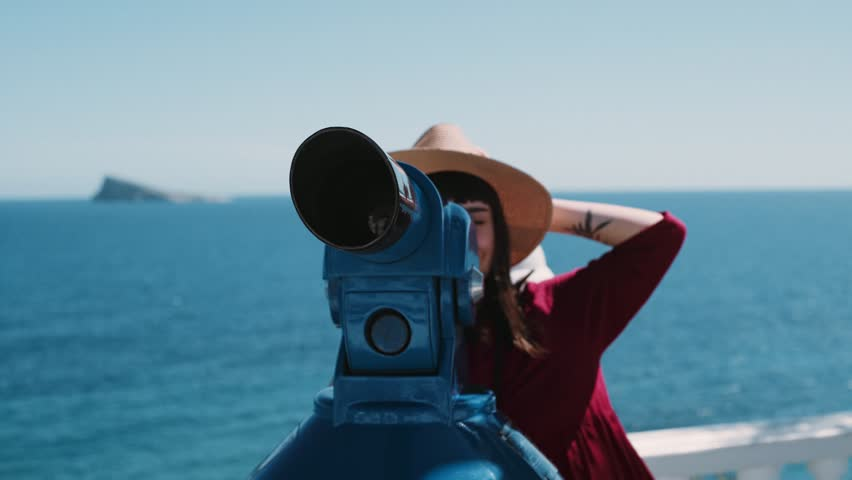 Beautiful hipster millennial woman in red dress and straw hat looks through pay per view telescope on beach promenade, summer breeze blows her hair, she smiles and laughs enjoying holidays