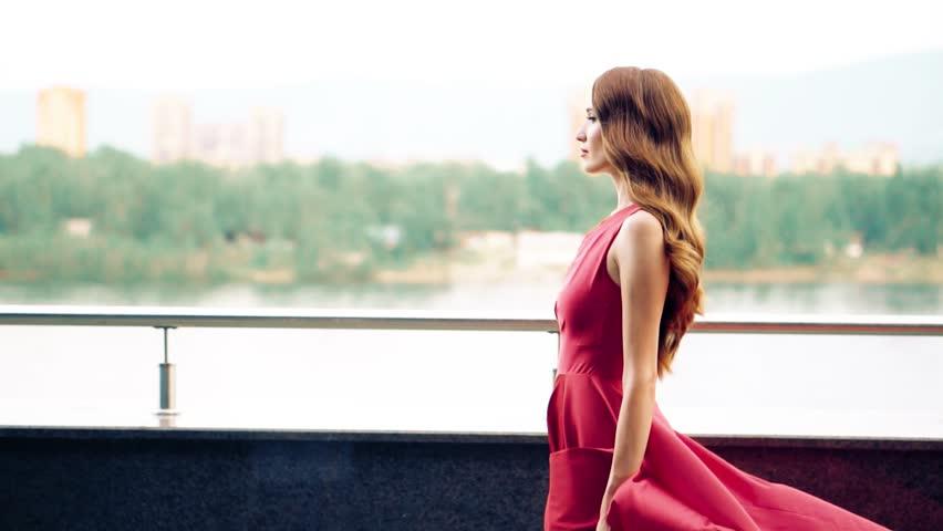 Beautiful woman in red fluttering dress. Urban background. Slow motion. #31307887