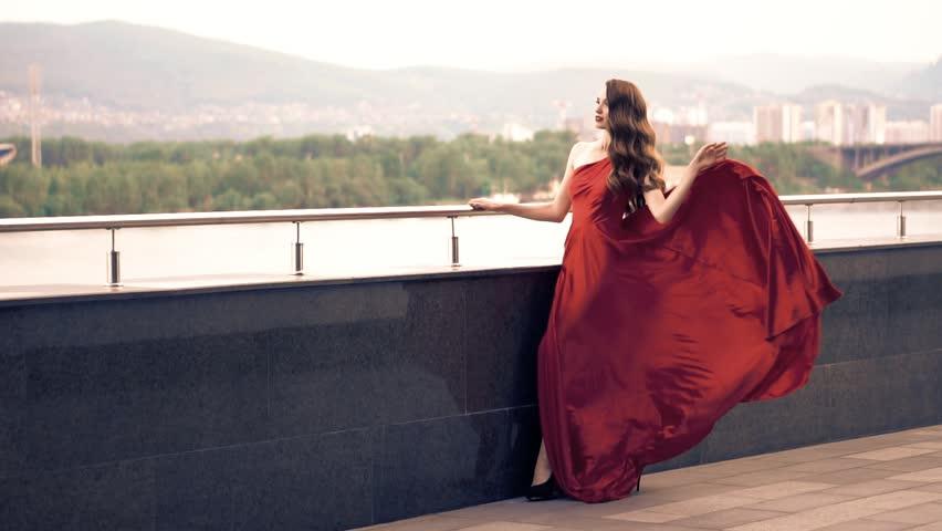 Beautiful woman in red fluttering dress. Urban background. #31307899