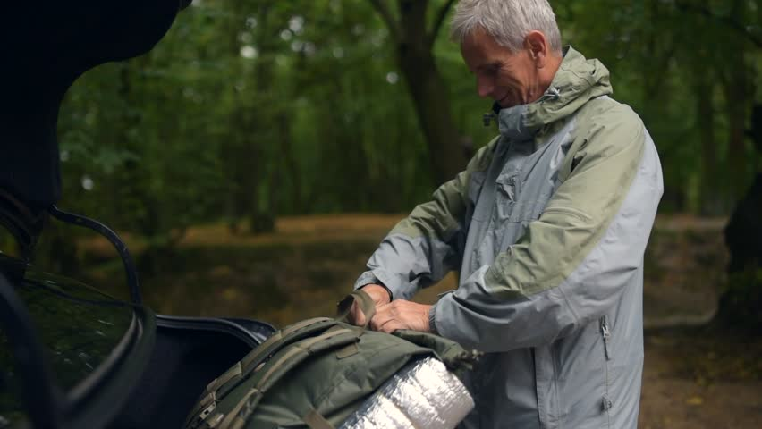 Nice aged man getting tourist equipment from the car boot | Shutterstock HD Video #31312699