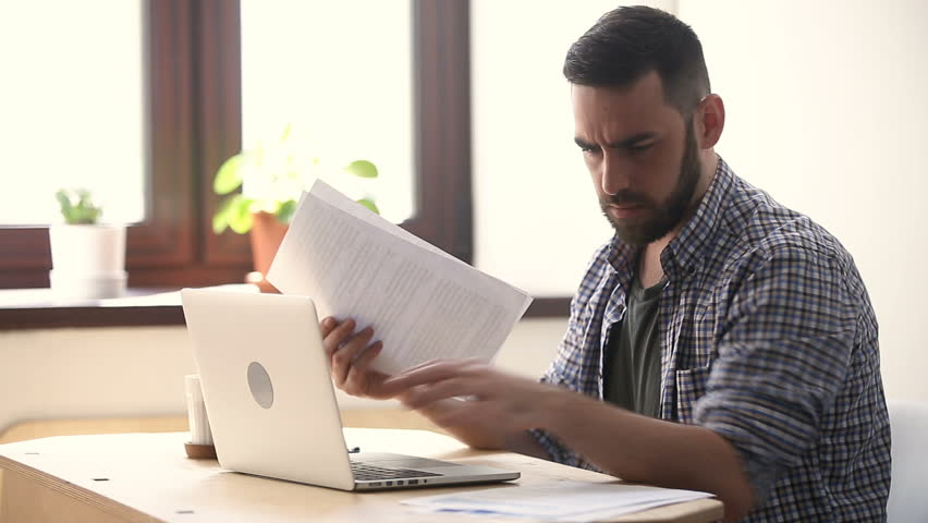Stressed unmotivated man confused by mistake in documents, looking through papers, frowning using laptop, failing urgent task, missing deadline, quits after bad work fed up with difficult job