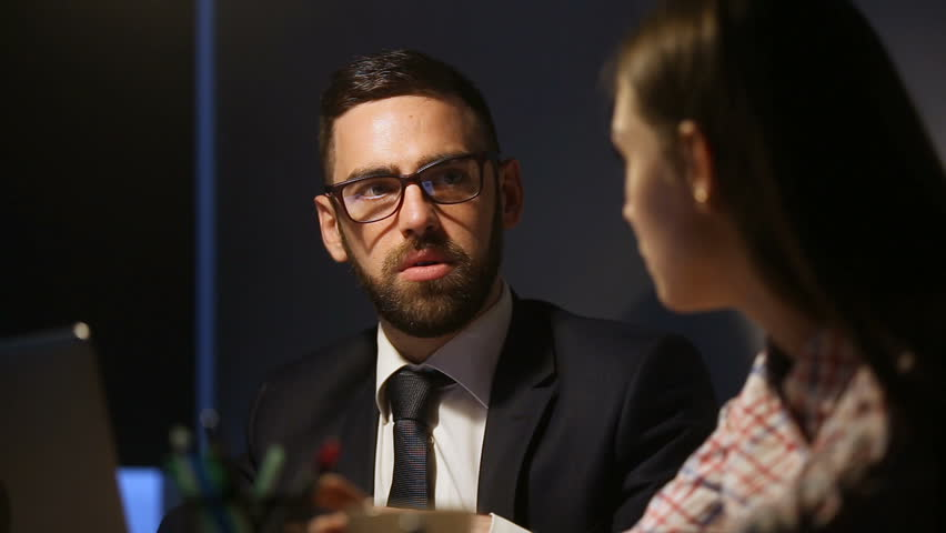 Serious businessman in suit and glasses discussing explaining business project to businesswoman, team of two businesspeople working late together in lamplight, partners talking sitting at office desk | Shutterstock HD Video #31314007