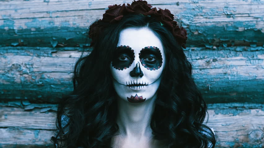 The Mexican Day of the Dead. The portrait of young woman with frightening make-up for Halloween on the background of wooden wall. 4K