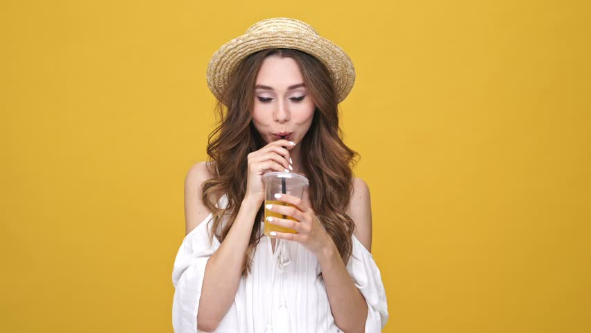 Pretty brunette woman in dress and hat drinking juice and dancing over orange background | Shutterstock HD Video #31321105