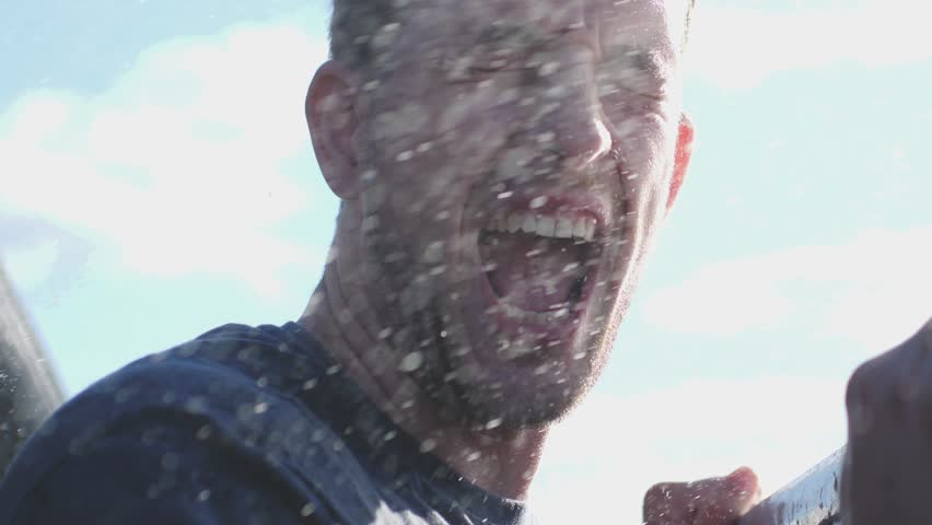 Water splashed in young happy man's face while man traveling on cruise ship in slow motion. 3840x2160