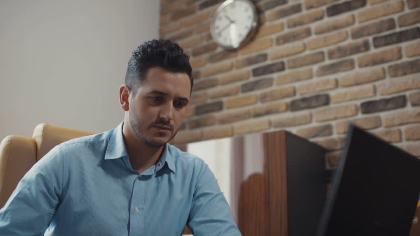 Young attractive bearded man uses a laptop working in the office in the background people. Shot on RED Epic Camera. | Shutterstock HD Video #31328278
