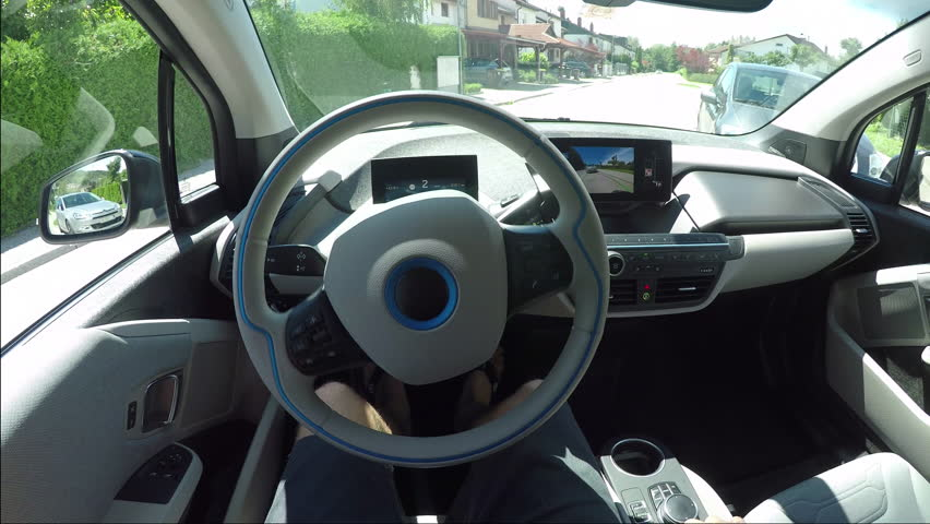CLOSE UP, POV: Man in futuristic automated electric car. Vehicle parallel parking by itself in suburban town street. Self-steering automatic computer vision auto turning wheel and parking on spot