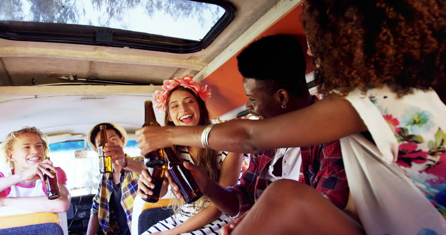 Group of friends toasting beer bottles in van 4k #31339486