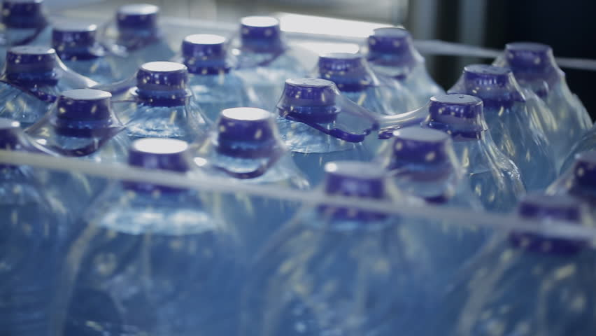 Plastic bottles with water in package, rotate in workshop of modern factory. Bottles with clean drinking aqua packed in cellophane transparent packaging for transportation are located in light | Shutterstock HD Video #31340356