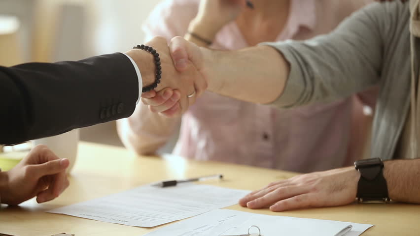 Couple sign mortgage contract, put signature on sale purchase rental agreement, handshaking realtor at meeting with estate agent, satisfied customers buy property, get keys of new home, close up view | Shutterstock HD Video #31351936