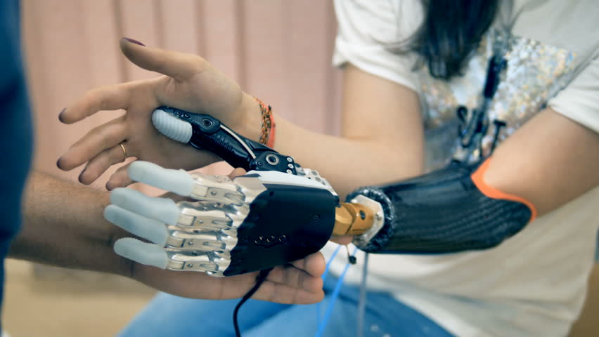 Young woman trying wireless bionic prosthesis. 4K.