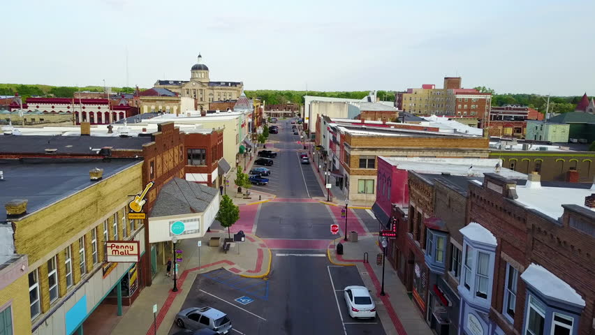 CIRCA 2010s - United States - A lovely aerial over a Main Stret in small town USA ends with two kids skateboarding down the empty boulevard.