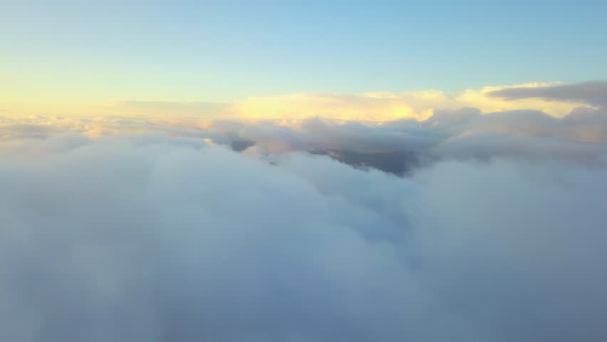Aerial drone view: flying in clouds. Beautiful sunset in the clouds. Above mountains. Amazing nature landscape. Concept: flying, airlines, afterlife, god, religion, organic clouds