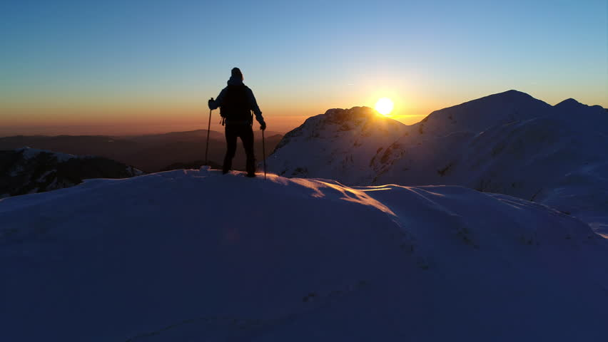 Aerial - Tracking shot and flyover young male mountaineer walking and stopping on mountain ridge in Julian Alps at colorful sunset (slow motion)