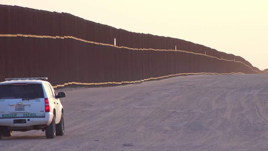 CIRCA 2010s - U.S.-Mexico border - Border patrol vehicle moves near the border wall at the US Mexico border at Imperial sand dunes, California.