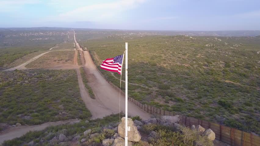CIRCA 2010s - U.S.-Mexico border - The American flag flies over the U.S. Mexico border wall in the California desert.
