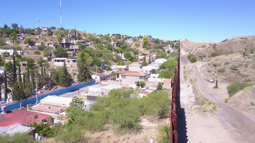 CIRCA 2010s - U.S.-Mexico border - Forward aerial along the U.S Mexican border wall fence reveals the town of Nogales.