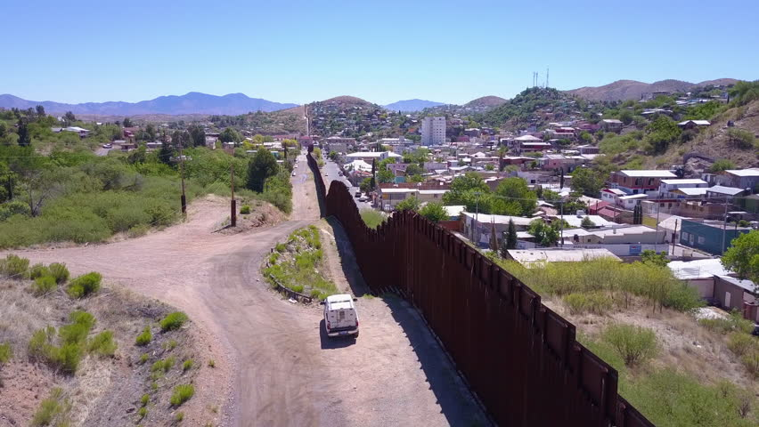 CIRCA 2010s - U.S.-Mexico border - Aerial over a border patrol vehicle standing guard near the border wall at the US Mexico border at Tecate.