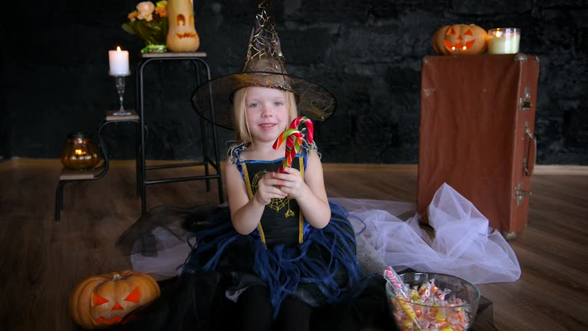 Little girl, little witch celebrate Halloween. Eat and scatter sweets. On a black background. jack lantern | Shutterstock HD Video #31375201