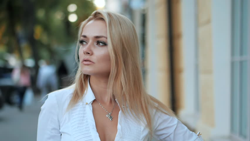 Portrait of young happy blonde businesswoman in the city. Slow motion. Beautiful girl in white sexy shirt in the street. #31376764