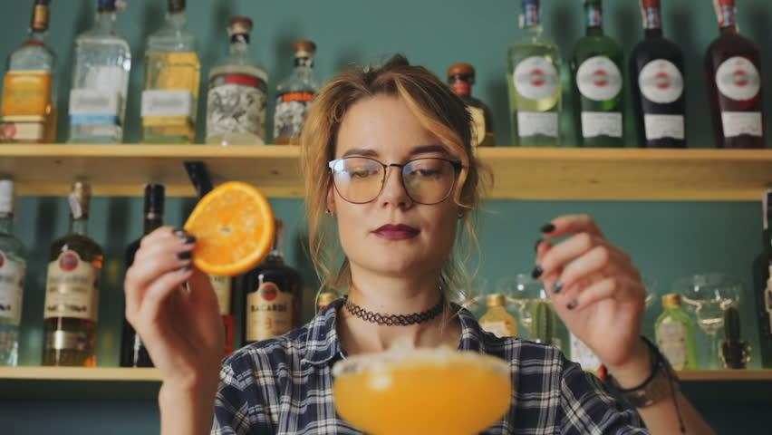 Female person barista professional barman waitress decorating cocktail orange straw alcohol bar counter bottles focus showing beautiful woman preparing alcoholic drink ingredients fruit juice liquor
