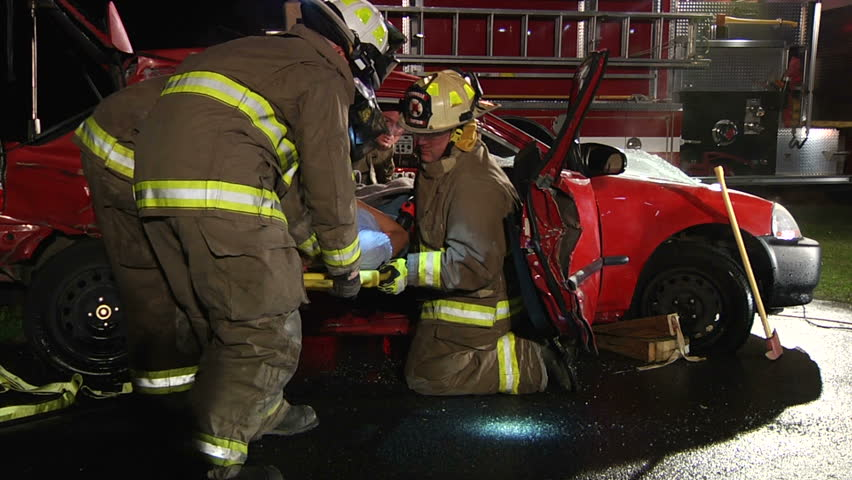 Car Crash Traffic Accident: Paramedics and Firefighters Plan Rescuing Passenger. Medics Prepare First Aid Equipment, Firemen Use Hydraulic Cutters Spreader. Dramatic night accident. Hero's in action.