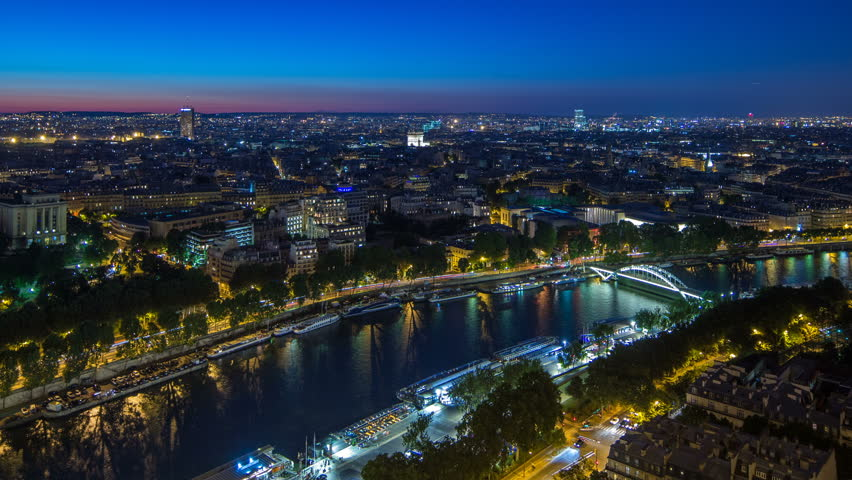 Aerial Night timelapse view of Paris City and Seine river shot on the top of Eiffel Tower observation deck. Evening illumination. Traffic on roads