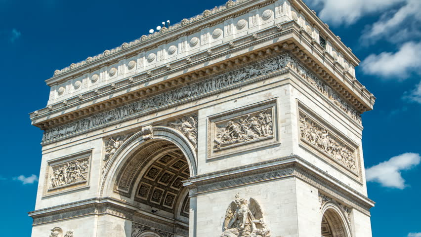 Top of the Arc de Triomphe (Triumphal Arch of the Star) timelapse is one of the most famous monuments in Paris, standing at the western end of the Champs-Elyseees. Blue cloudy sky at summer day