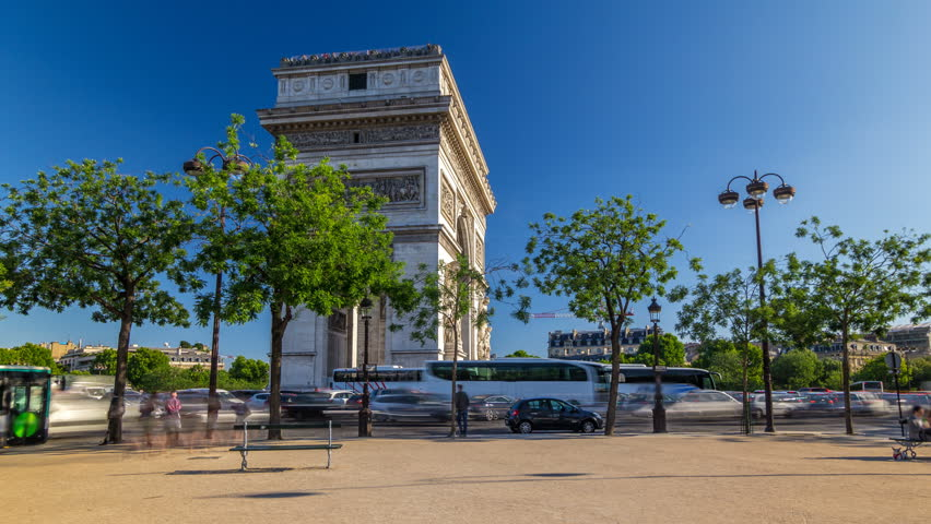 The Arc de Triomphe (Triumphal Arch of the Star) timelapse hyperlapse is one of the most famous monuments in Paris, standing at the western end of the Champs-Elyseees. Traffic on circle road. Blue