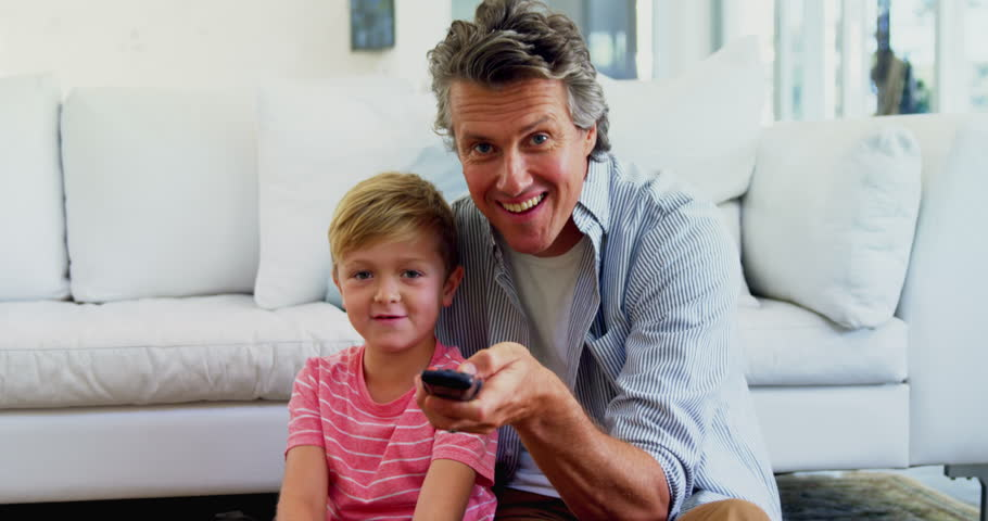 Father and son watching television in living room at home 4k #31424116