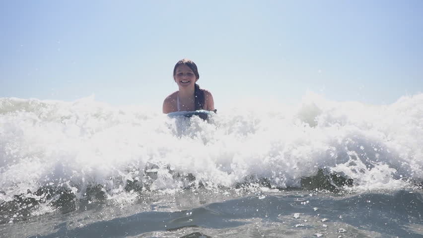 Youth bodyboarding in ocean waves at Myrtle Beach SC vacation. Children having fun playing in ocean waves surfing on bodyboards. Riding waves at Myrtle Beach South Carolina.    Shutterstock HD Video #31445098