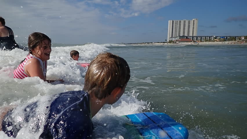 Youth bodyboarding in ocean waves at Myrtle Beach SC vacation. Children having fun playing in ocean waves surfing on bodyboards. Riding waves at Myrtle Beach South Carolina.    Shutterstock HD Video #31445110
