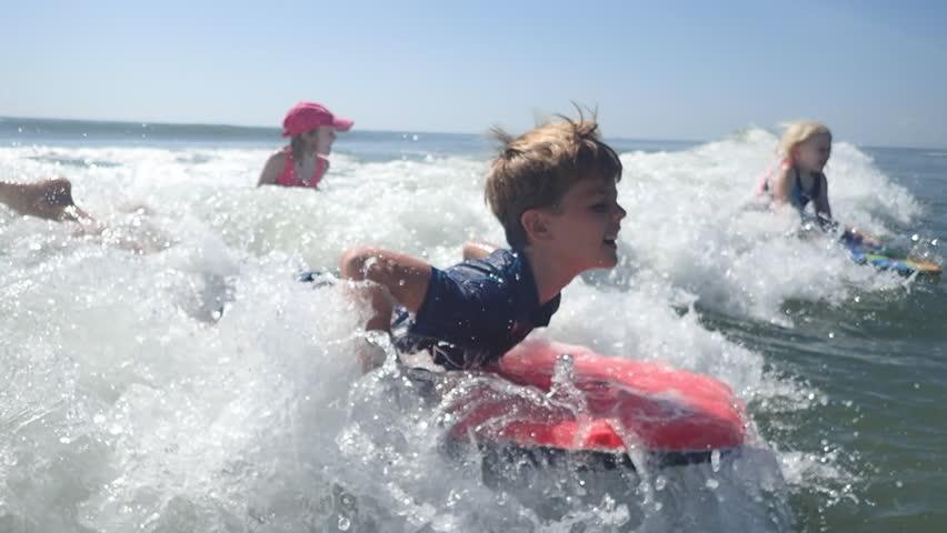 Children bodyboarding in ocean waves at Myrtle Beach SC vacation. Family having fun surfing together at Myrtle Beach SC. Ocean fun and family time in water. Children playing in ocean.