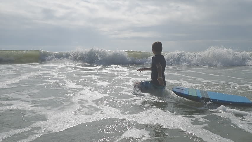 Youth bodyboarding in ocean waves at Myrtle Beach SC vacation. Children having fun playing in ocean waves surfing on bodyboards. Riding waves at Myrtle Beach South Carolina.    Shutterstock HD Video #31445143