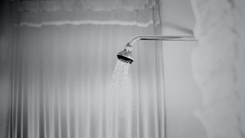 Water running from a rain shower in a bathroom, a classic timeless creepy horror film-noir scene.