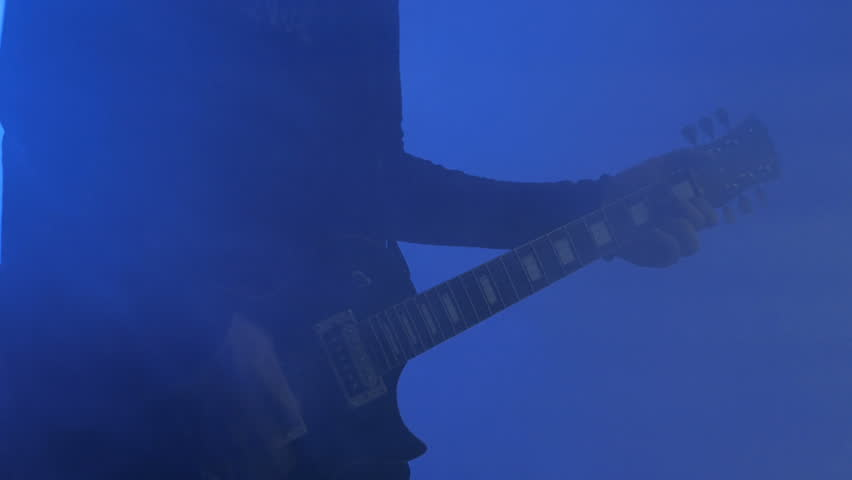 Close up shot of man playing guitar on concert stage. Smoke, strobing blue light. Entertainment and art concept | Shutterstock HD Video #31461526