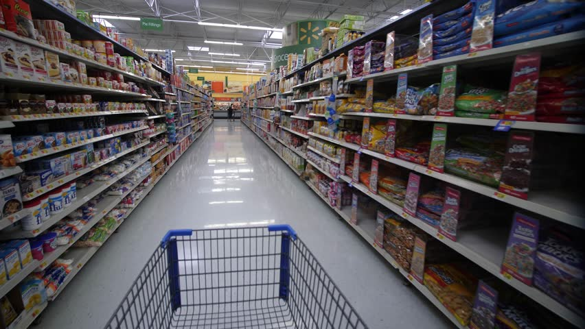 TAMPA, FLORIDA - AUGUST 2017: Shopping Inside Walmart -  Steadicam POV of Aisle with canned food, dry snacks, baking flour etc.
