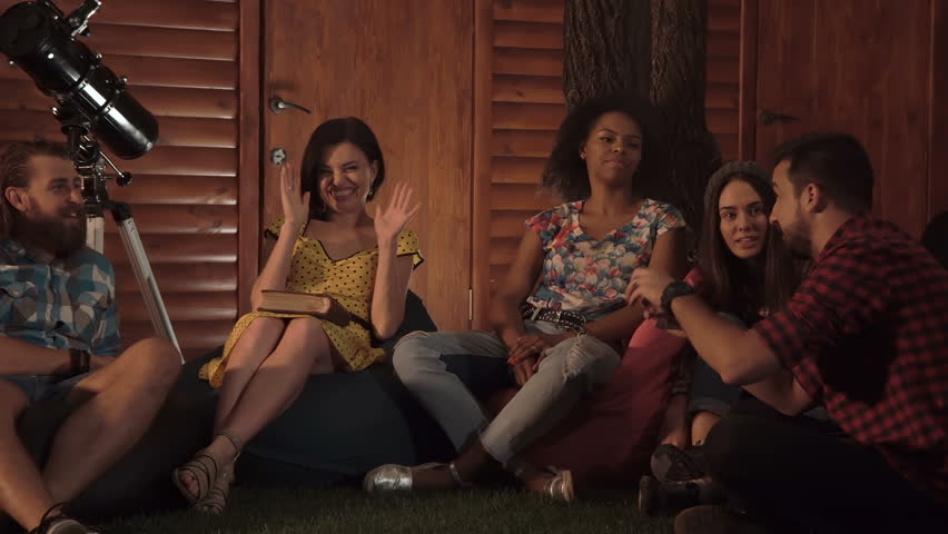 Adult bearded men tells some fun story to diverse mixed ethnic group of friends on porch in evening on backyard. | Shutterstock HD Video #31497055