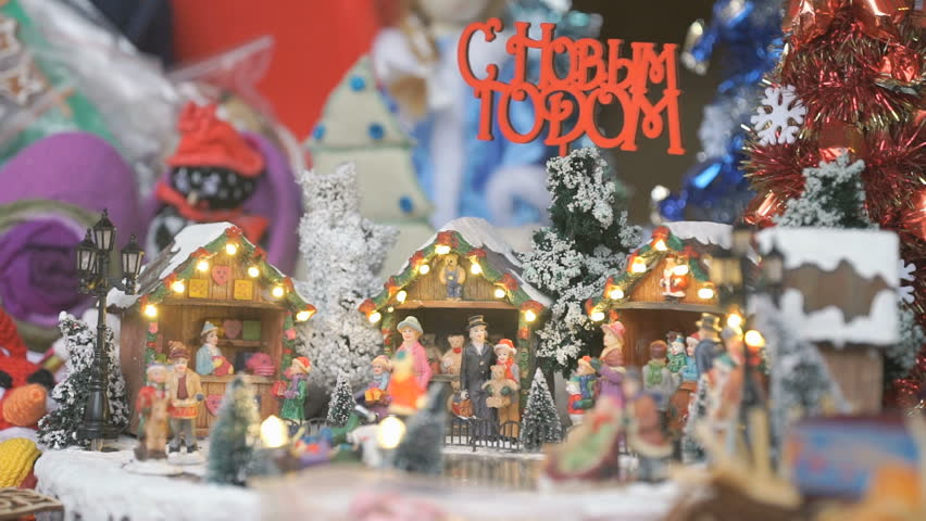 Close-up of miniature souvenir Christmas toy. Little people skate in circle on an ice rink with winter scenery with the inscription in Russian HAPPY NEW YEAR. Female hand taking action figure #31501291