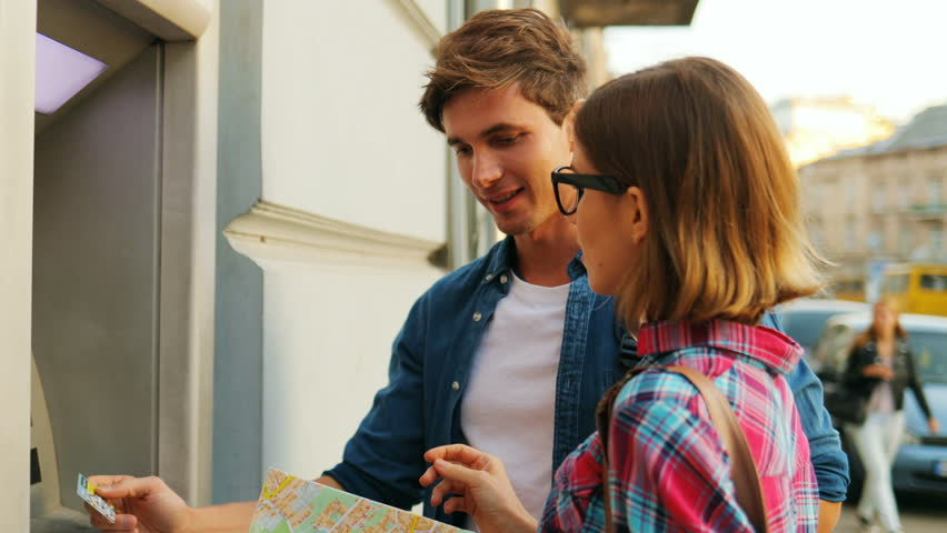 Cheerful couple looking happily at each other in front of the ATM machine while a young man is tryinh to withdraw money from ATM machine. Attractive caucasian woman is holding a city map. Outdoors. Royalty-Free Stock Footage #31515448