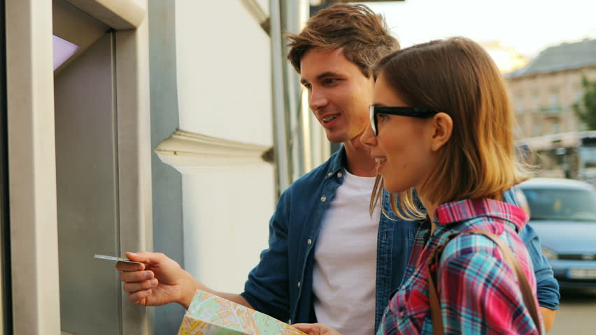 Touristic couple looking happily at each other in front of the ATM machine. Attractive caucasian woman is holding a city map. Outdoors. Royalty-Free Stock Footage #31515511