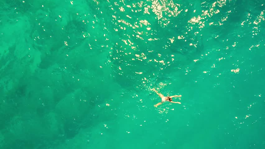 Aerial top down shot of a young woman swimming in the sea | Shutterstock HD Video #31517497